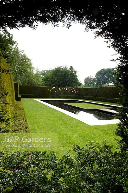 Contemporary water feature - pool with floating stepping stone path to central grass area and metal sculptures