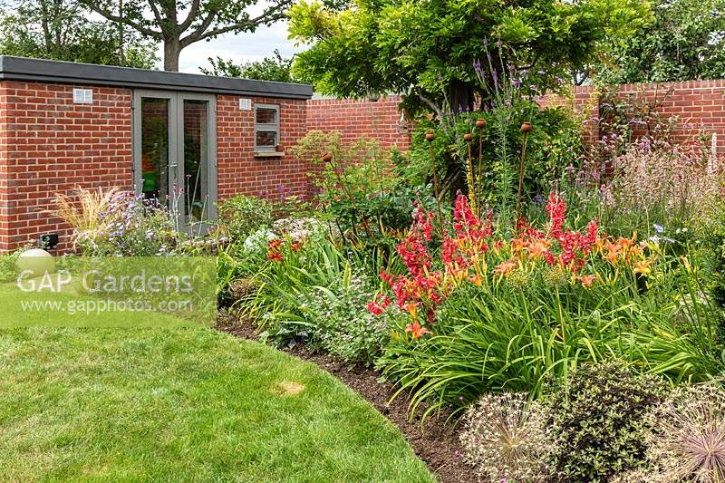 A curved border with mixed summer perennial planting including Penstemon and Hemerocallis, edged by a curving lawn and leading to a small brick building