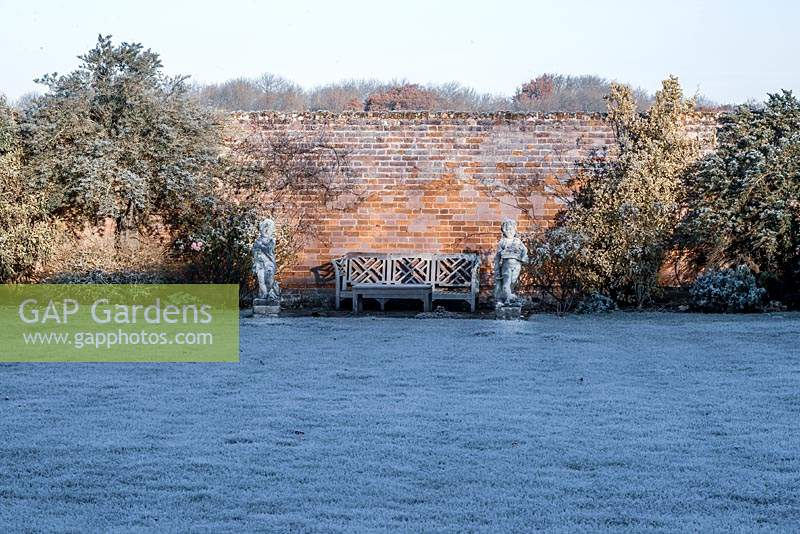 View across frosty lawn to bench and statues in front of old brick wall.