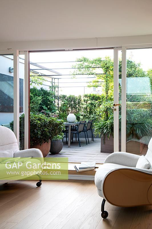 View from inside through open glass doors to outdoor roof garden, a dining corner under a metal pergola and screed by plants