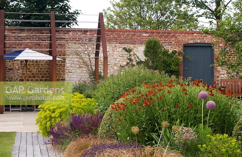 Corten steel pergola above seating area against brick wall of a walled country garden, in foreground corner of a perennial flower bed