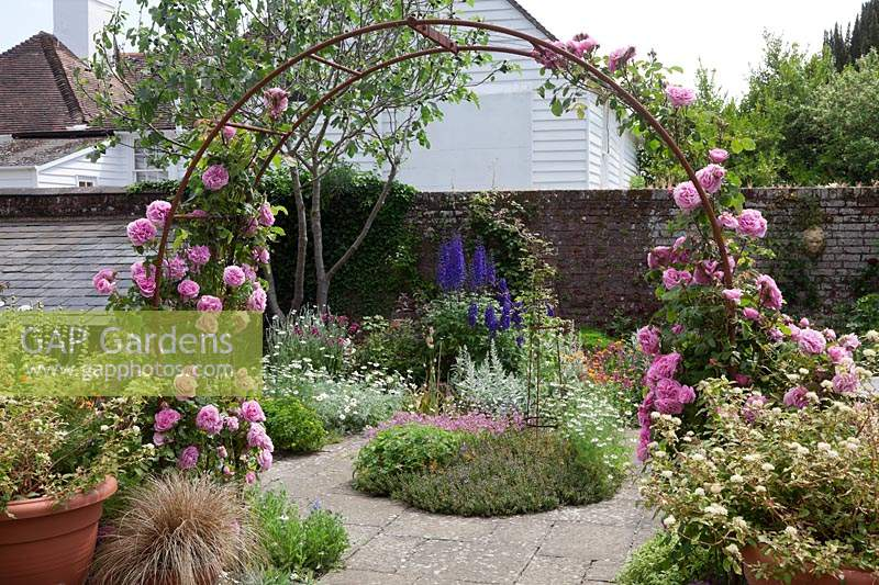 A rusty metal rose arch festooned with Rosa 'Gertrude Jekyll' - Climbing Rose. Set in small courtyard with flower beds, plants: Delphinium 'Black Knight', Geum ' Prinses Juliana', Penstemon 'Garnet', Nigella damascena 'Miss Jekyll' - Love in the Mist, Anthemis, Lychnis coronaria,  Artemisia ludoviciana 'Valerie Finnis'