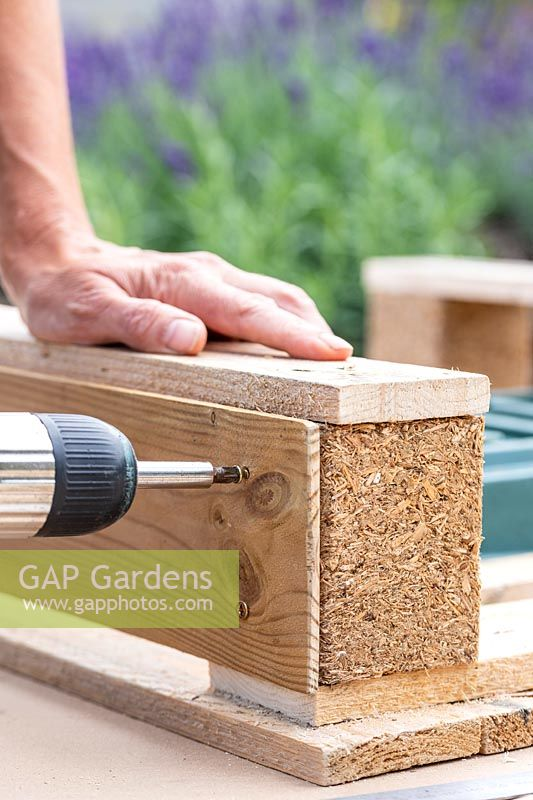 Woman using an electric screwdriver to fix planks on to the sides of the pallet to hide the planting trays.