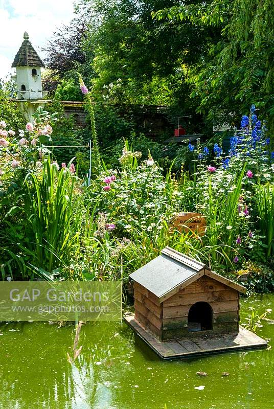 Duck house on pond with marginal plants and perennial border with dovecote beyond - Open Gardens Day, Great Finborough, Suffolk