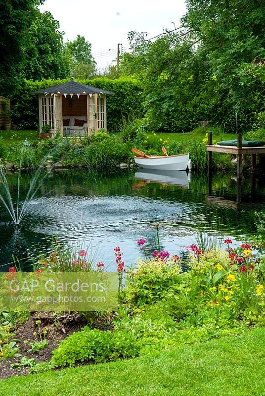 Garden pond with border of Primulas and Astilbes, small  fountain and dinghy moored alongside jetty. Summerhouse on far bank - Open Gardens Day, Palgrave, Suffolk
