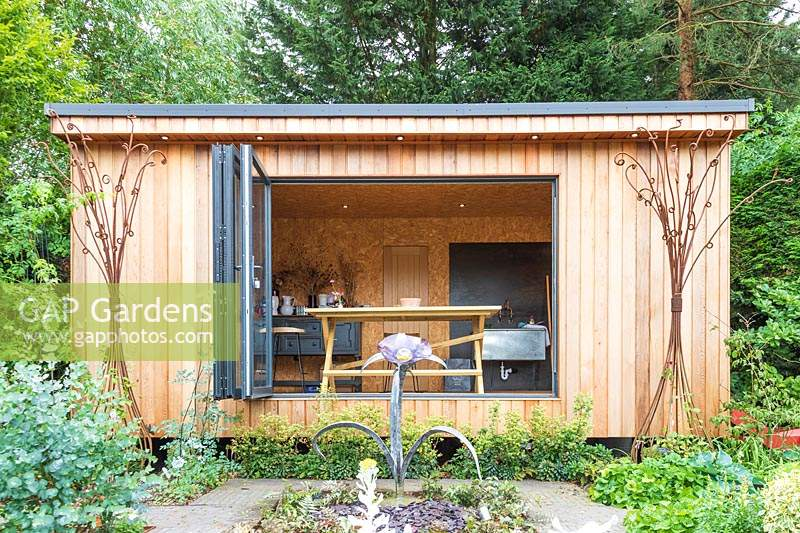 Wooden cantilevered workshop with open bifold doors