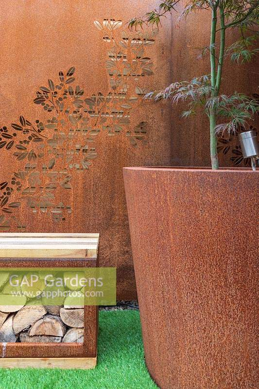 Corten steel screen, pots and bench with storage for for firewood