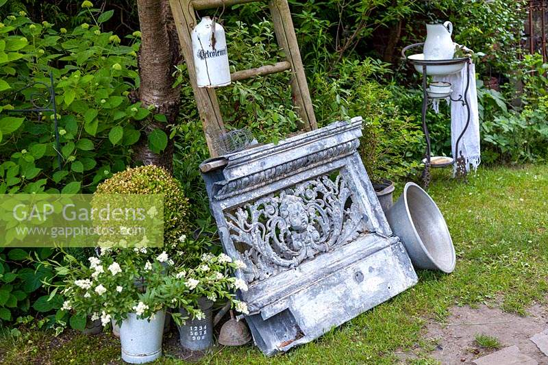 Display of vintage objects, potted plants and antique washstand