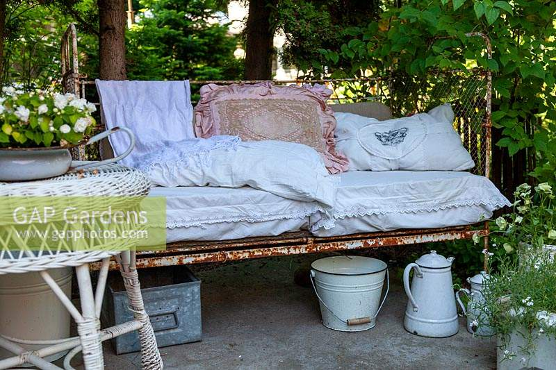 Old bed frame as a bench, pillows and a wicker table in the foreground