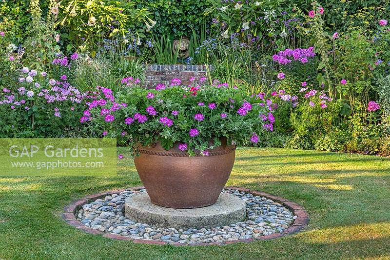 Focal point pot on circular base set into lawn, colour themed borders behind