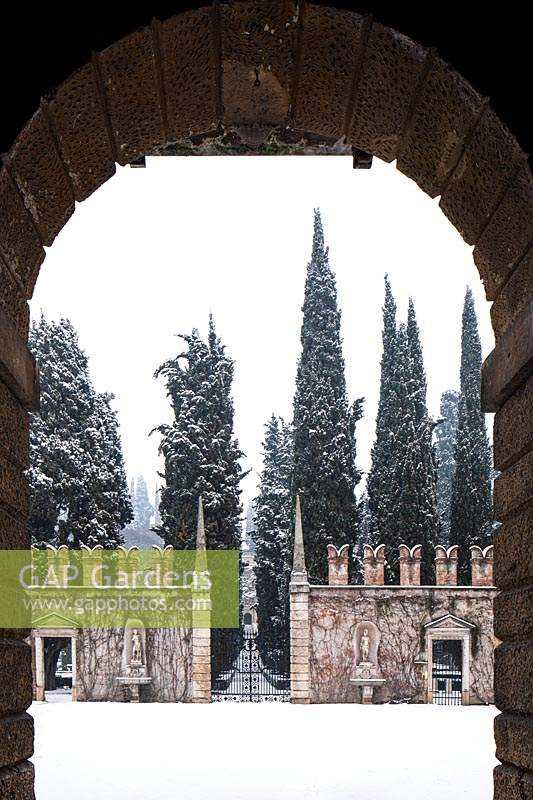 View through arch to court of honor and avenue of cypresses at Giardino Giusti, Verona