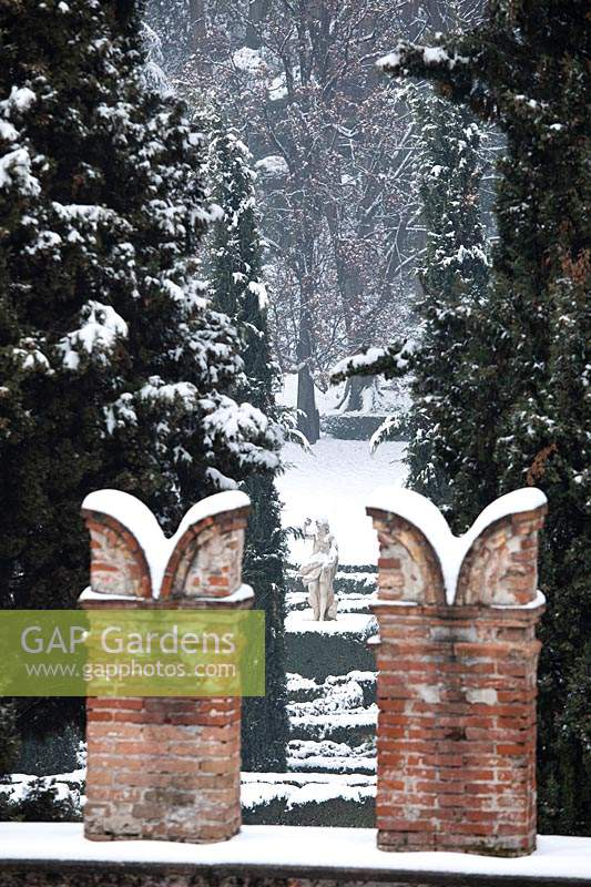 Decorative brick chimney pots with view to sculpture in snow covered garden