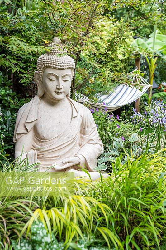 Buddha sculpture in small garden with exotic planting