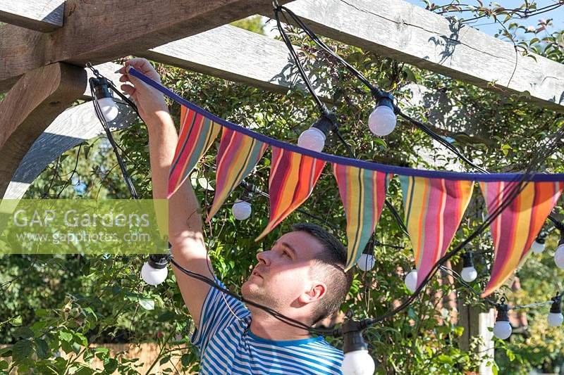 Man hanging up colourful bunting on underside of pergola