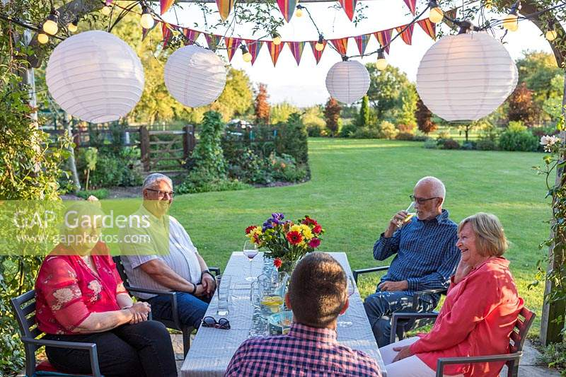 People at dining table enjoying snakcs and drinks underneath a wooden pergola decorated with light chains and colourful bunting