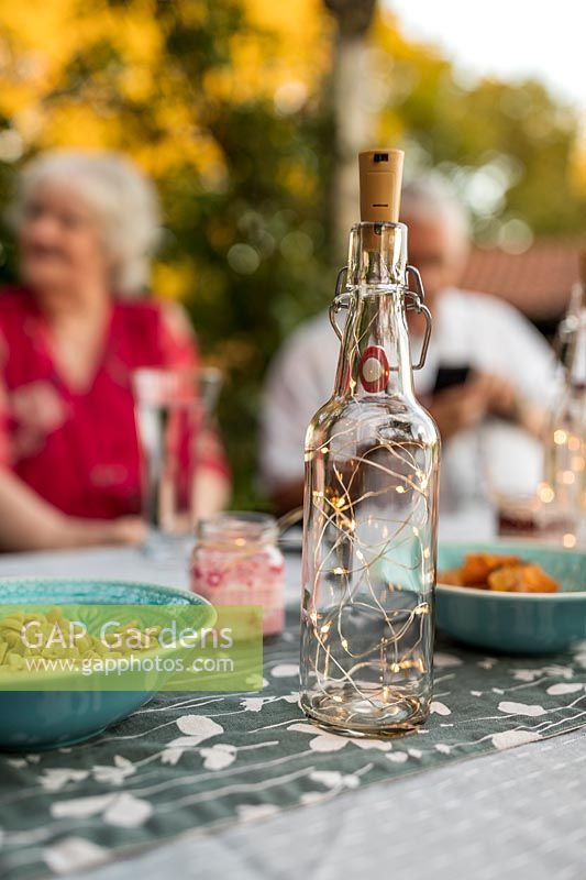 Glass bottles with light chains inside used as table decoration for evening garden party