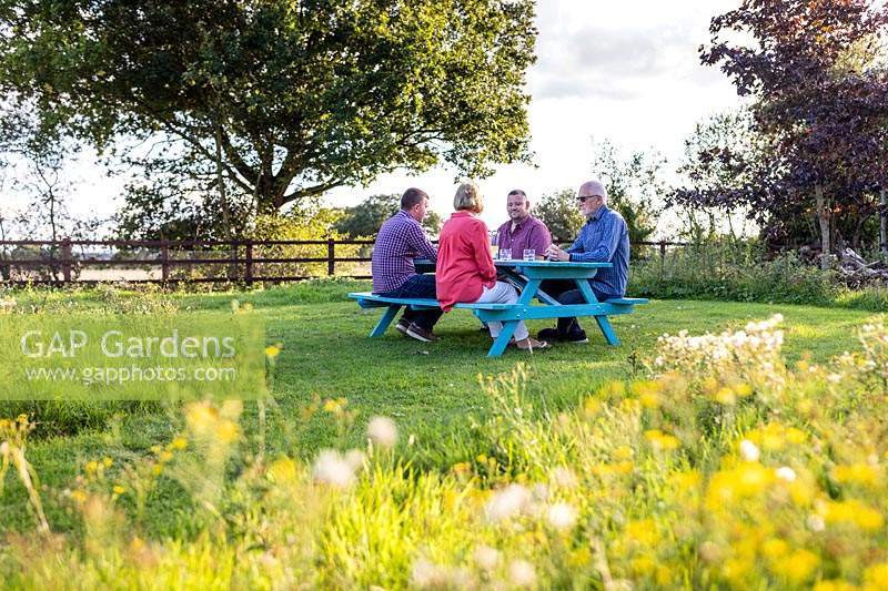 People sat at newly assembled picnic bench in meadow