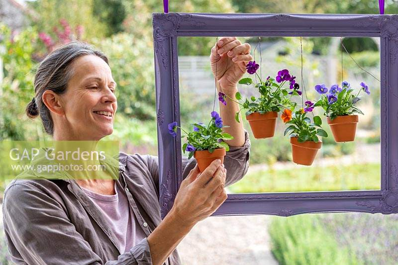 Woman adjusting the wires to arrange the hanging pots within the frame