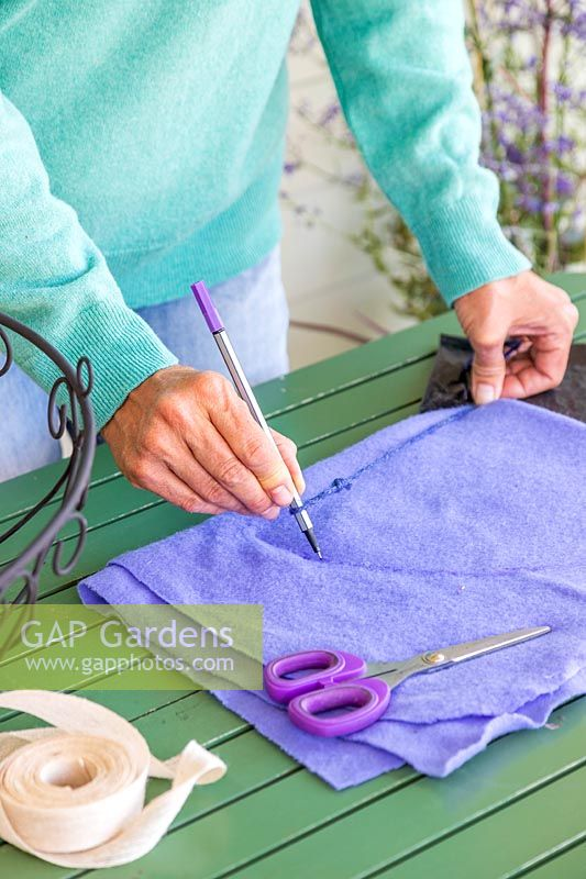 Woman using string and pen to mark a quarter circle on a folded piece of purple material