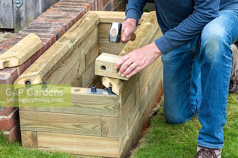 Person building raised timber bed.