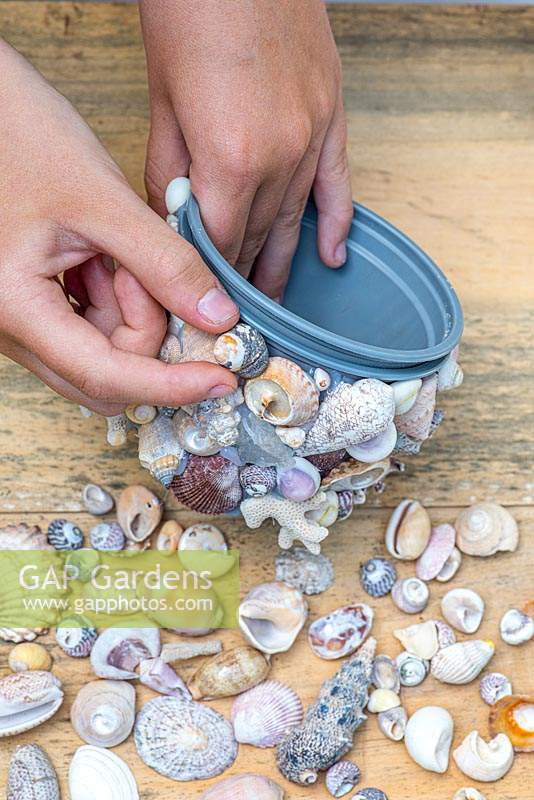 Building up a coat of shells, using a hot glue gun to secure each in place on a plastic plant pot