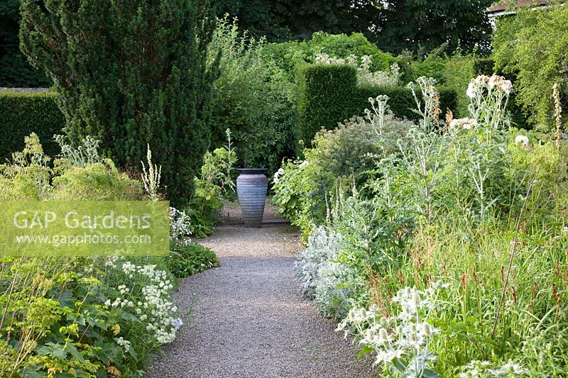 Formal path to decorative urn in the White Garden. Loseley Park, Surrey