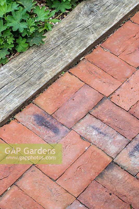 Red brick path edged with oak sleeper.