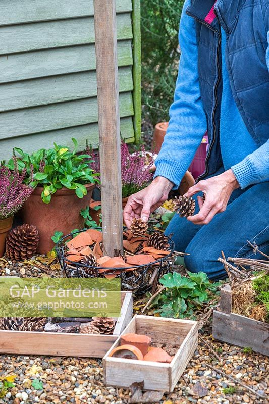 Woman adding pine cones suitable for insects to overwinter to the bottom basket.
