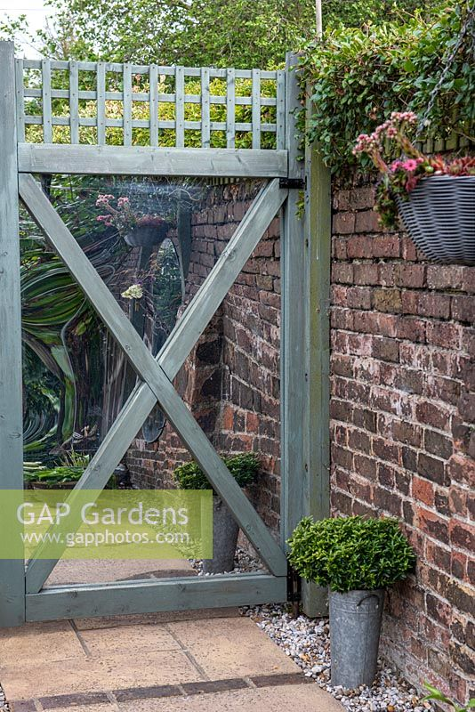 A wooden gate is fitted with mirror panels, to reflect the garden and create an impression of a garden beyond.