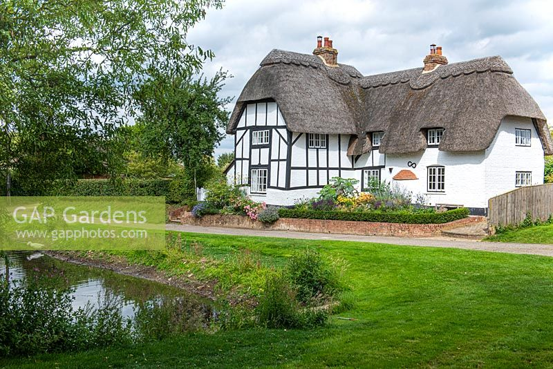 View from an ancient village duck pond to an old thatched cottage with a contemporary front garden