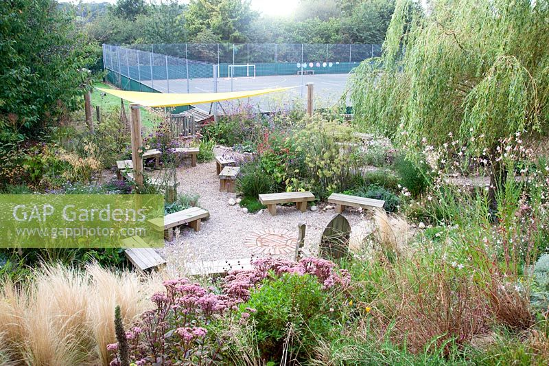 Looking down on wooden seating area amongst late summer planting. Sedlescombe Primary School, Sussex, UK.