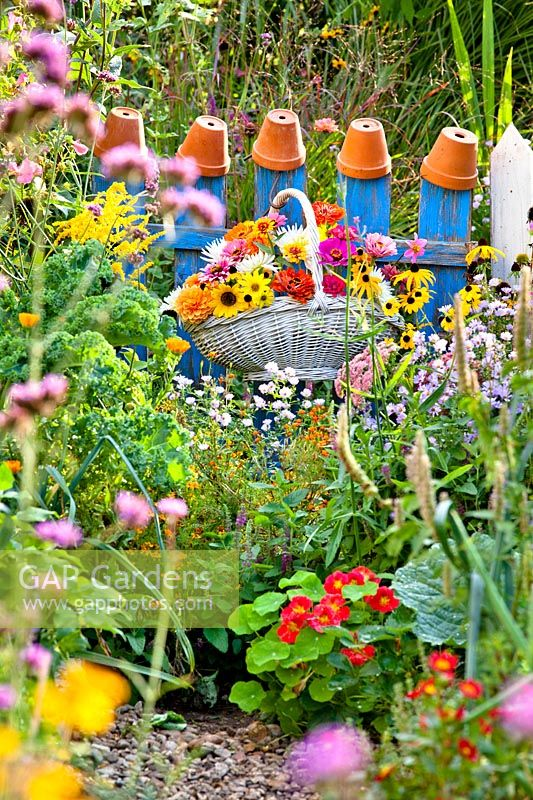 Trug basket with summer flowers hanging on a blue wooden fence