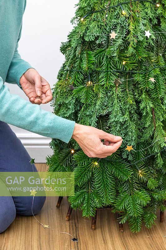 Woman decorating space saving Christmas tree with gold stars on a string