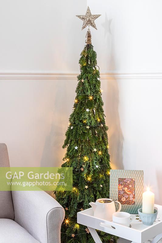 Space saving Christmas Tree made with pine - Abies and conifer - Juniperus foliage attached to a willow obelisk and decorated with star decorations and lights in a modern living room setting with chair and side table