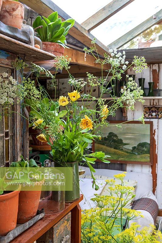 Old fashioned garden room, or potting shed, filled with vintage gardening equipment and paraphanalia, cut flowers in vase