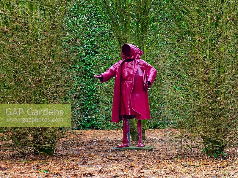 The Paper Lady sculpture, viewed through Hornbeam arch at East Ruston Old Vicarage garden, Norfolk, UK.