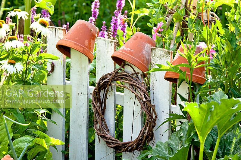 White gate with wreath and upturned terracotta pots.