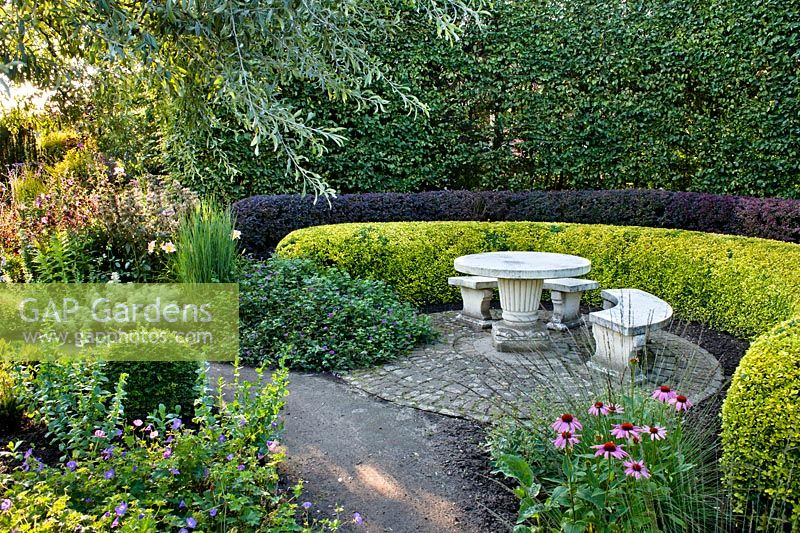 Tiered curved hedges around a circular paved area with stone furniture