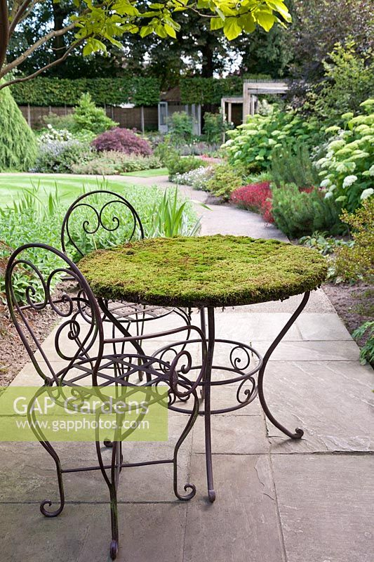 A shady garden feature of green moss growing on a cast iron metal round table with chairs on patio - July