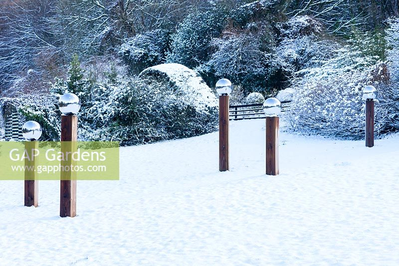 Avenue of wooden pillars topped with stainless steel globes in the Meadow covered with snow. Veddw House Garden