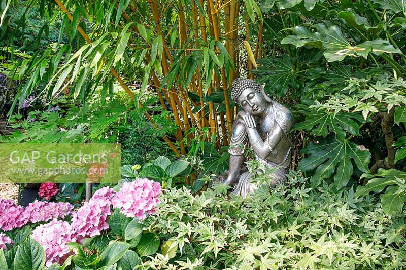Seated statue surrounded by Bamboo and other foliage plants