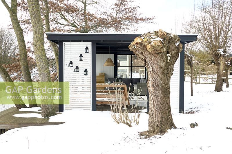 Gardenhouse with comfortable lounge furniture near frozen lake in the middle of snow. Big knotted willow tree in front