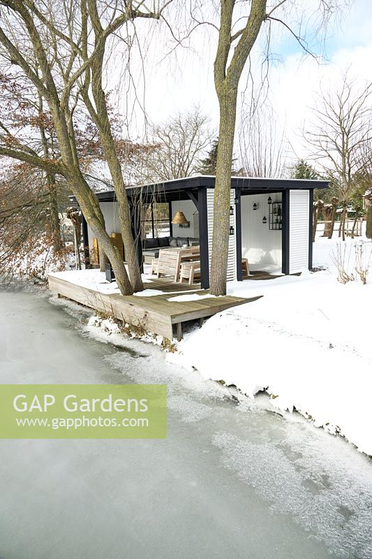 Summerhouse with comfortable lounge furniture on the edge of a frozen lake in the middle of a snow covered area