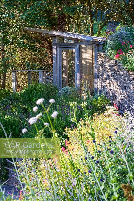 Summerhouse near stone wall surrounded by planting, flower bed in foreground
