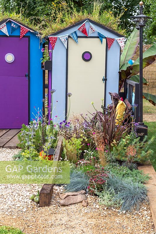 Colourful beach huts with wildflower green roofs. Fun on Sea, RHS Hampton Court Palace Flower Show, 2017. Design: Tony Wagstaff.