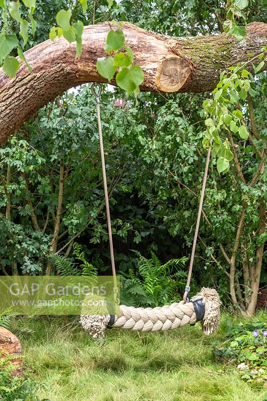 Children's rope swing in shady woodland garden. The Zoflora and Caudwell Children's Wild Garden. RHS Hampton Court Palace Flower Show, 2017. Designers: Adam White and Andree Davies.