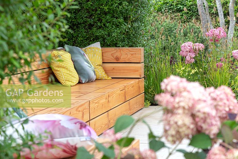 Wooden bench with cushions. 'A Place to Meet' Garden. Hampton Court Flower Show, 2017. Designed by The Association of Professional Landscapers.