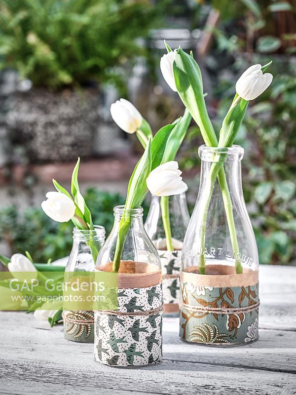Tulips in vases of milk bottles wrapped with decorative papers.