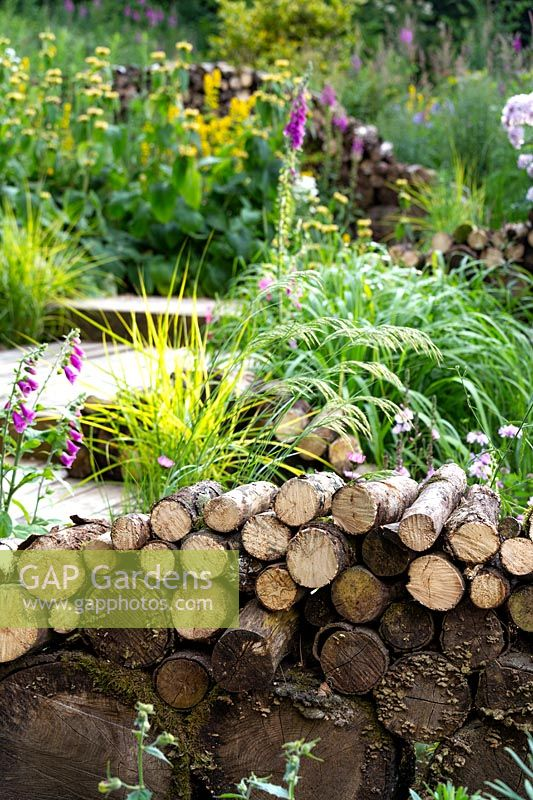 An insect and wildlife friendly log wall in front of naturalistic borders planted with perennials and ornamental grasses.