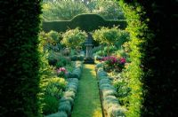 View through yew hedge to formal herb garden at Cranbourne Manor in Dorset